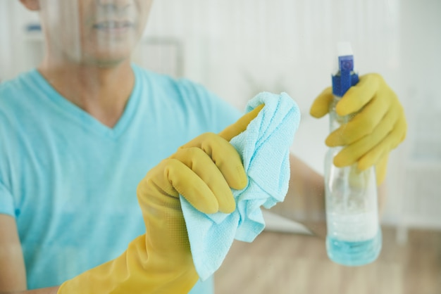 Unrecognizable man in gloves spraying window with cleaning liquid and wiping with cloth Free Photo