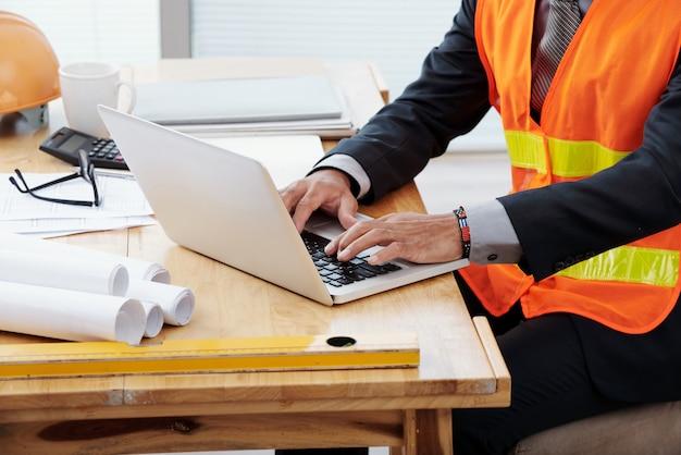 Uomo irriconoscibile in giubbotto di sicurezza al neon e tailleur seduto alla scrivania e usando il portatile Foto Gratuite