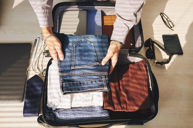 Unrecognizable man packing suitcase for business trip Free Photo