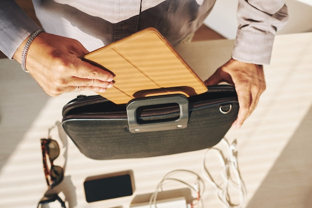 Unrecognizable man putting tablet computer into briefcase Free Photo