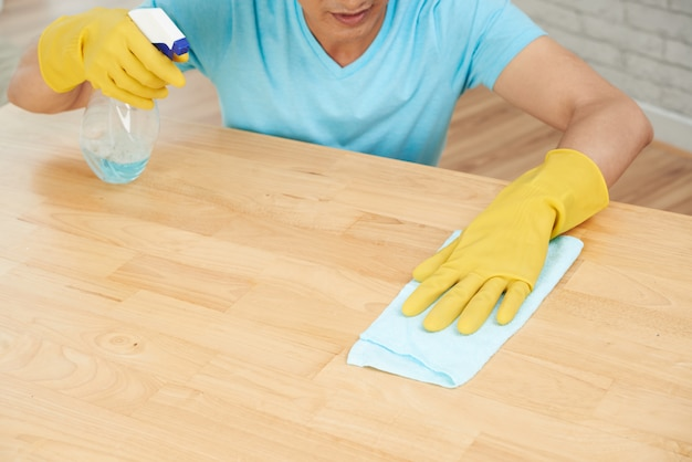 Unrecognizable man in rubber gloves spraying table and cleaning with cloth Free Photo