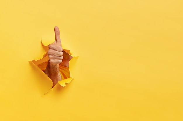 Unrecognizable man shows like gesture through torn yellow wall, keeps thumb up Free Photo