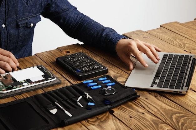 Unrecognizable man uses laptop to find guides how to repair electronic device tool bag and broken gadget near on vintage wooden table Free Photo