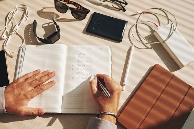 Unrecognizable man writing plan in journal and gadgets lying around on desk Free Photo