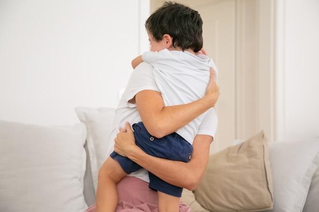 認識できない母親が愛情のこもった素敵な息子を抱き締めたり抱きしめたりします。 無料写真