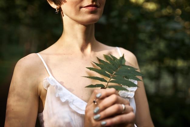 緑のシダの葉を持って、一人で森の中を歩いている短い髪型と薄い肌を持つ認識できない神秘的な若い女性。 無料写真