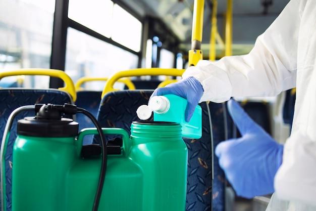 コロナウイルスに対する消毒を開始するためにタンクリザーバーに消毒剤を追加する手袋をした白い防護服を着た認識できない人のクリーナー。 Premium写真