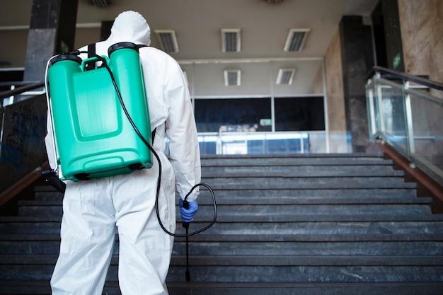 Persona irriconoscibile in tuta di protezione chimica bianca con serbatoio che disinfetta il corridoio pubblico per fermare la diffusione del virus corona altamente contagioso Foto Gratuite