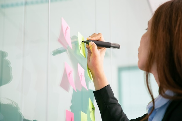 Unrecognizable red-haired businesswoman writing on sticker with marker Free Photo