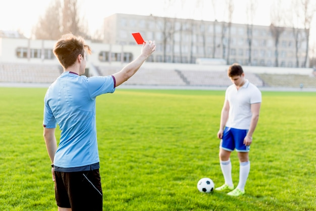 Unrecognizable referee showing red card to young sportsman Premium Photo