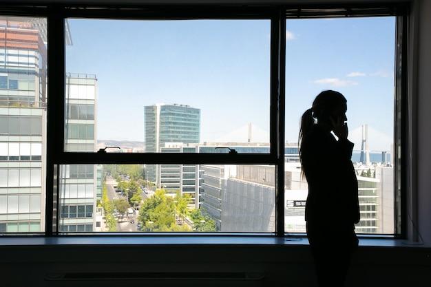 Siluetta irriconoscibile della donna di affari che sta vicino alla finestra e che parla sul telefono cellulare. manager professionista in ombra e paesaggio urbano. business, comunicazione e concetto di azienda Foto Gratuite