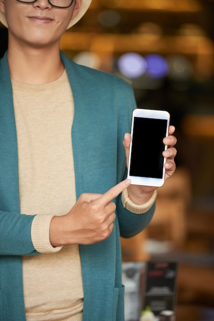 Unrecognizable stylish man standing in cafe, holding smartphone and pointing to screen Free Photo