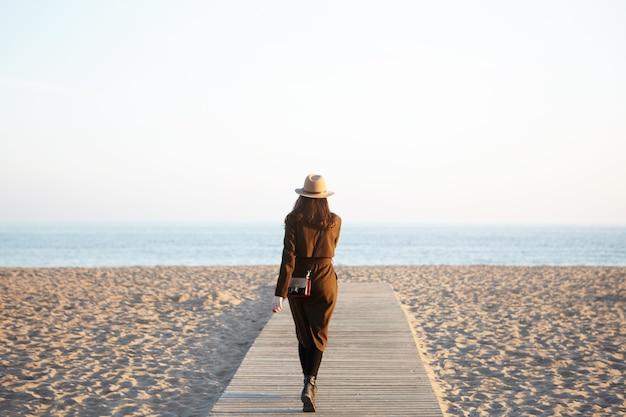 帽子、ロングコート、遊歩道を歩いているショルダーバッグを身に着けている認識できないスタイリッシュな女性 無料写真