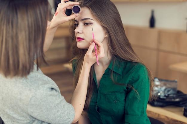 Unrecognizable stylist using eyeliner on model Free Photo