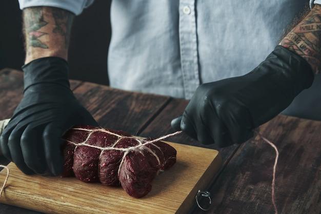 Неузнаваемый татуированный мясник в черных перчатках связывает кусок мяса веревкой, чтобы выкурить его на деревянных Бесплатные Фотографии
