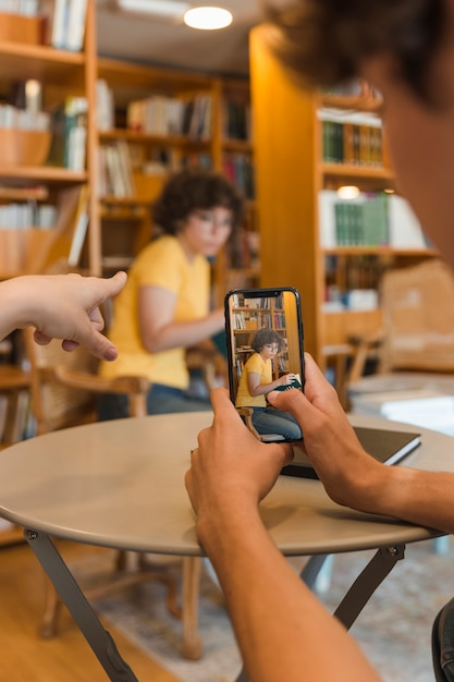 Unrecognizable teenagers taking picture of studying classmate Free Photo