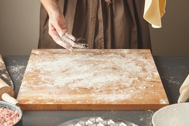 Una donna irriconoscibile aggiunge un po 'di farina bianca sulla tavola di legno mentre tiene in aria la pasta appiattita per la pasta o gli gnocchi. guida passo passo alla cottura dei ravioli Foto Gratuite