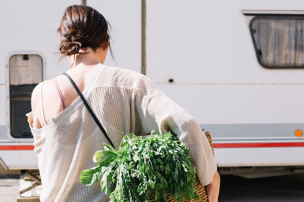Unrecognizable woman carrying basket with vegetables Free Photo