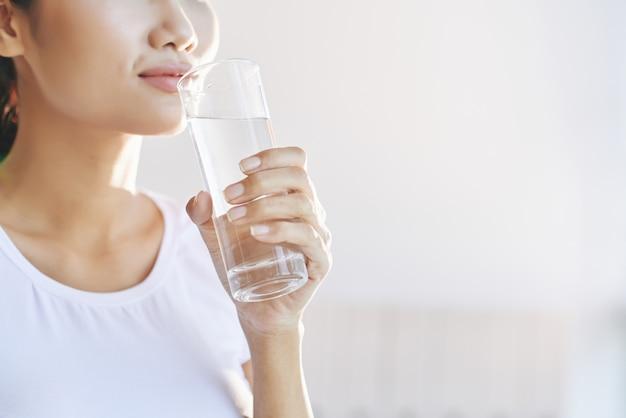 인식 할 수없는 여자 입에 물 한 잔을 들고 무료 사진