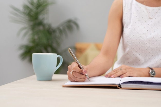 Unrecognizable woman in dress sitting indoors at desk and writing in journal Free Photo