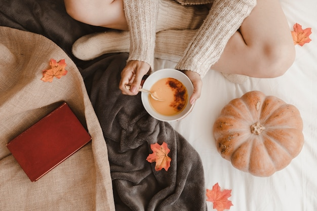 Unrecognizable woman eating near pumpkin and book Free Photo