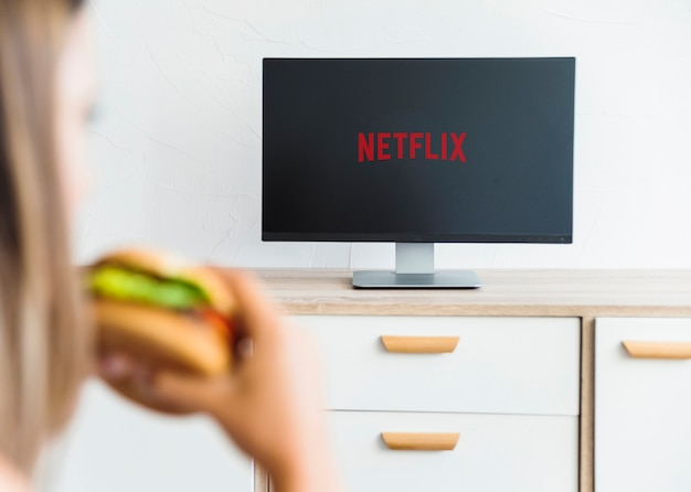 Unrecognizable woman eating and watching series in living room Free Photo