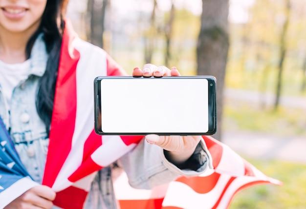 アメリカの国旗と携帯電話を保持している認識できない女性 無料写真