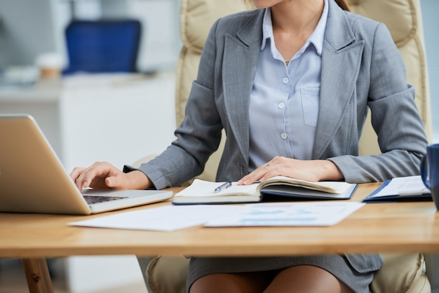 До неузнаваемости женщина в деловом костюме сидит за столом и работает на ноутбуке Бесплатные Фотографии