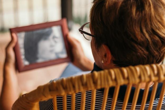Неузнаваемая женщина ищет антикварную фотографию, когда была маленькой Premium Фотографии