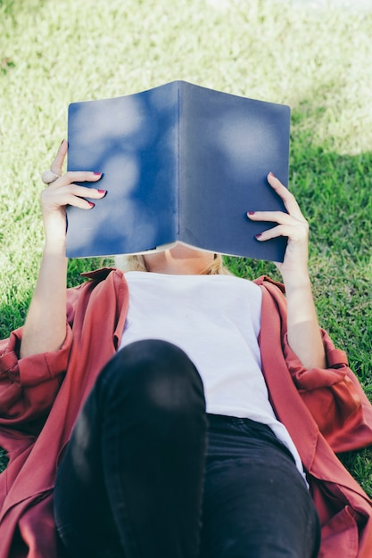 Unrecognizable woman reading on grass Free Photo