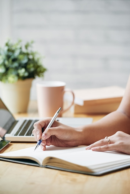 Unrecognizable woman sitting at desk indoors and writing in planner Free Photo