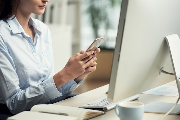 Unrecognizable woman sitting in office in front of computer and using smartphone Free Photo
