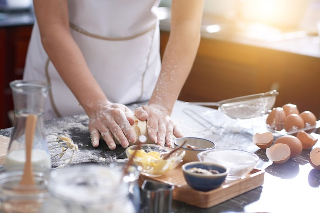 Unrecognizable woman standing at kitchen table and kneading dough by hand Free Photo