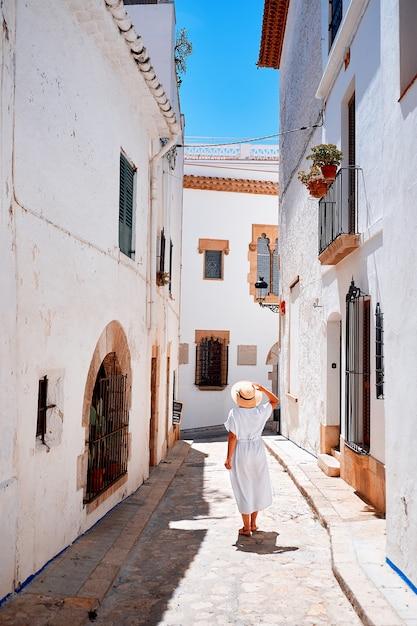 An unrecognizable woman summer trip. back view of woman walks the narrow european streets. outdoors shot. Premium Photo