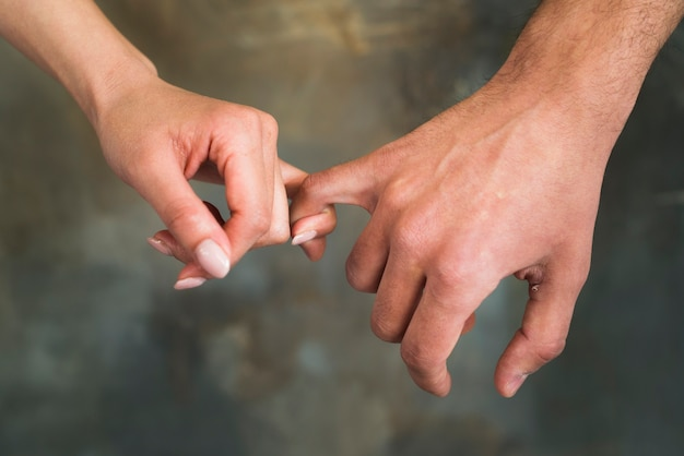 Unrecognizable young lovers holding little fingers Free Photo