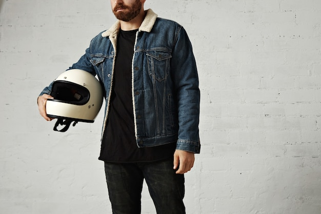 Unrecognizable young motor biker wears shearling denim jacket and black blank henley shirt, hugs his vintage beige motorcycle helmet, isolated in center of white brick wall Free Photo