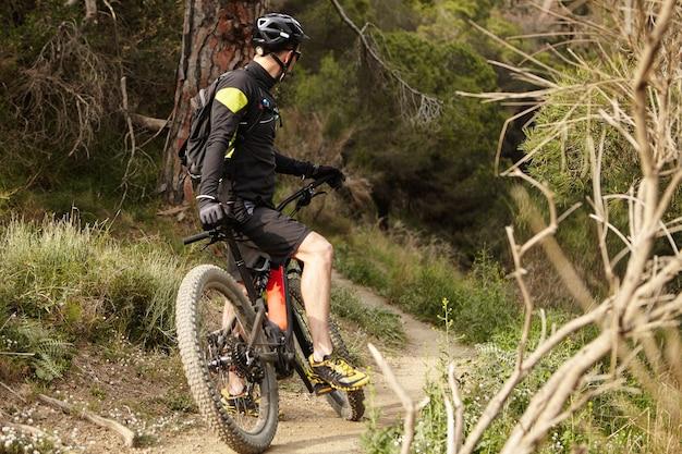 Irriconoscibile giovane mountain biker in abbigliamento da ciclismo nero tenendo il piede sul pedale Foto Gratuite