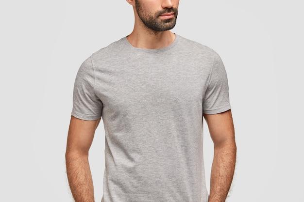 Uomo barbuto irriconoscibile vestito con una maglietta grigia casual Foto Gratuite