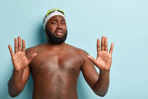 L'uomo con la barba lunga del nuotatore afroamericano mostra il gesto di stope con avversione, rifiuta qualcosa, mostra i palmi alla macchina fotografica Foto Gratuite