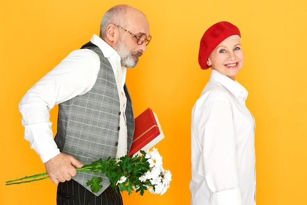데이지와 초콜릿 한 덩어리를 들고 우아한 옷을 입은 형태가 이루어지지 않은 대머리 노인이 매력적인 아내에게 생일 선물을 만듭니다. 사람, 나이, 결혼 및 관계 개념 무료 사진
