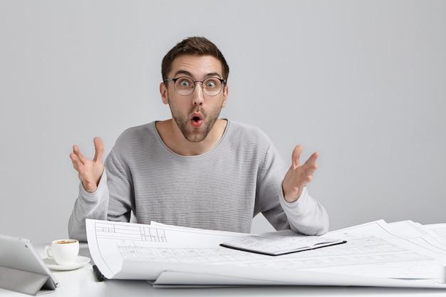 Designer maschio sorpreso con la barba lunga al banco di lavoro, gesti in espressione scioccata, guarda gli occhi buggati Foto Gratuite