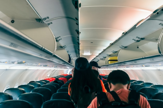 Unspecified passengers were walking out of the plane following the exit sign Premium Photo