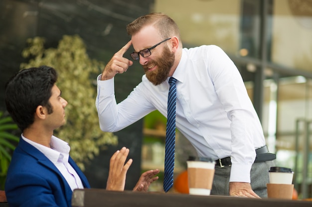 Unstable bearded boss gesturing at head while screaming Free Photo