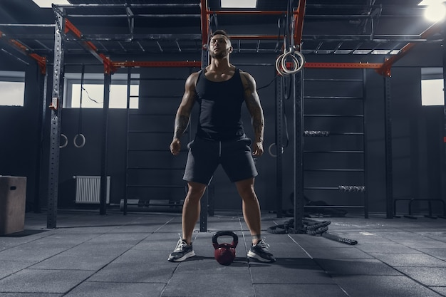 Unstoppable. young muscular caucasian athlete practicing squats in gym with the weight. male model doing strength exercises, training lower body. wellness, healthy lifestyle, bodybuilding concept. Free Photo