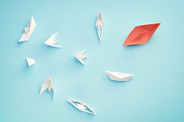 Unsuccessful leadership concept. red paper boat and a lot of sinking ships Premium Photo