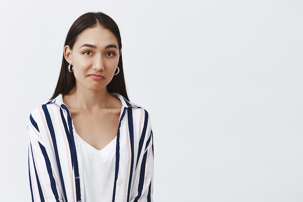 Unsure attractive and fashionable woman in striped blouse, pursing lip and gazing questioned, hesitating and wanting to reject offer politely, being displeased Free Photo