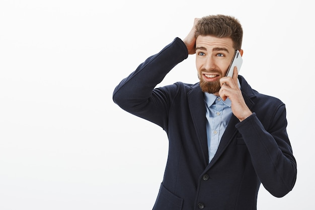 灰色の壁を越えて遅く働くために携帯電話を介して頭を悩まスマホでスクラッチ頭を悩ましている問題を抱えた顔でひげを左に見てエレガントなスーツを着た混乱している魅力的な男性起業家 無料写真