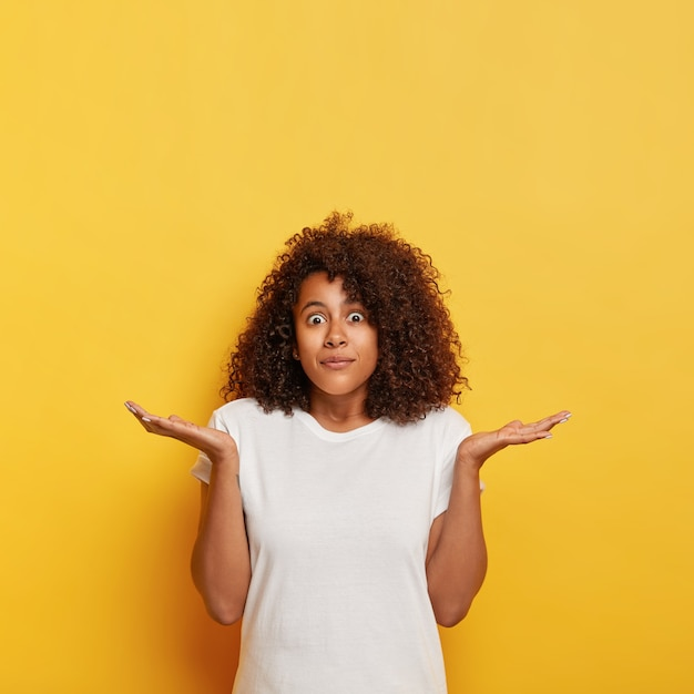困惑した女子学生が手のひらを横に広げ、目がバグで見つめ、無知で気づかず、黒い巻き毛をしていて、白いtシャツを着て、黄色い壁にポーズをとって、上向きに空きスペースがある 無料写真