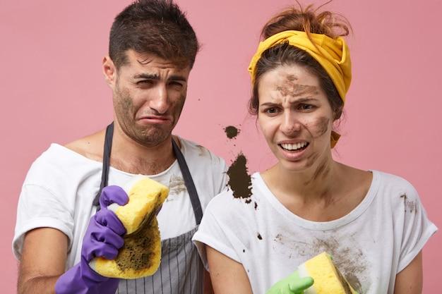 Maschio e femmina disordinati che fanno le faccende domestiche pulendo le finestre guardando la macchia nera con uno sguardo disgustoso cercando di spazzarla via con le spugne. persone, famiglia, lavoro domestico, concetto di pulizia Foto Gratuite