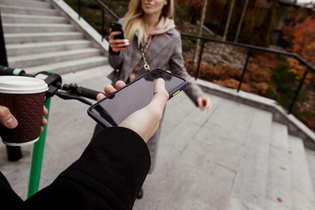 Необычное романтическое свидание на электросамокатах. вид от первого лица. человек, держащий смартфон с пустой копией космического экрана, чашки кофе и колеса. женщина, стоя рядом с телефоном в руке и улыбается. Premium Фотографии